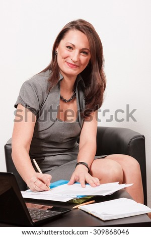 Smiling woman sitting by desk with some documents