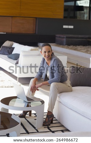 Smiling woman sitting in a sofa with laptop on coffee table. Large view. - stock photo