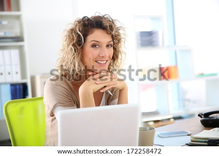 Smiling woman sitting in front of laptop computer - stock photo