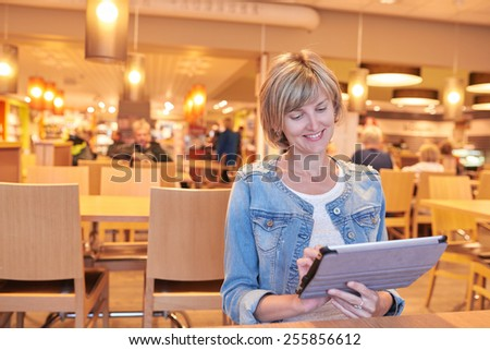 Smiling woman sitting in the cafe using digital tablet - stock photo