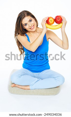Smiling woman sitting on a floor in yoga pose, holding fruit smile. White background isolated. Female young model. - stock photo