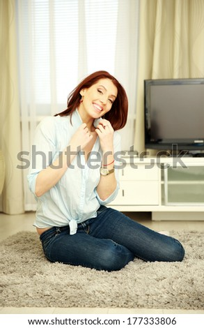 Smiling woman sitting on the carpet at home - stock photo