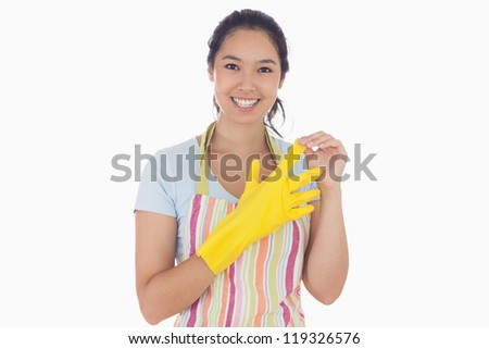 Smiling woman standing and taking off rubber gloves while wearing an apron - stock photo
