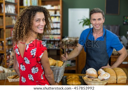 Smiling woman standing at bakery counter in supermarket - stock photo