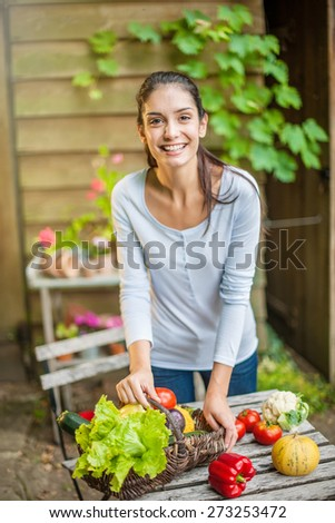 Smiling woman standing in front the garden table with a basket of fresh vegetables