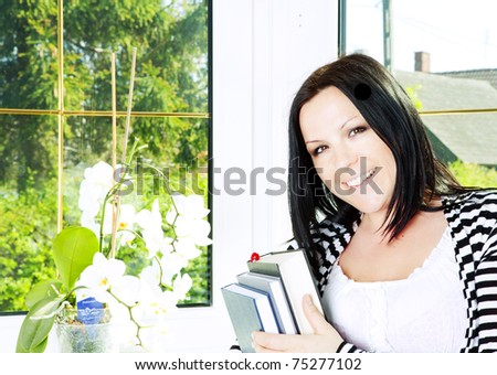 smiling woman standing near window and holding books - stock photo