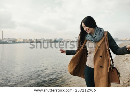 smiling woman standing on the river bank  - stock photo