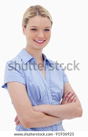 Smiling woman standing with arms folded against a white background
