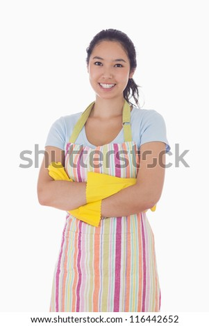 Smiling woman standing with crossed arms and wearing apron and rubber gloves - stock photo