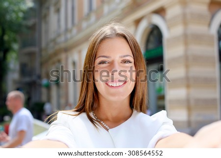Smiling woman taking a selfie photo in an urban street  - stock photo