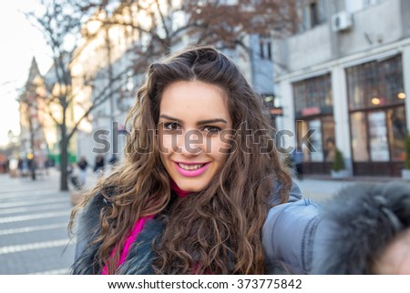 Smiling woman taking a selfie photo in an urban street in winter - stock photo