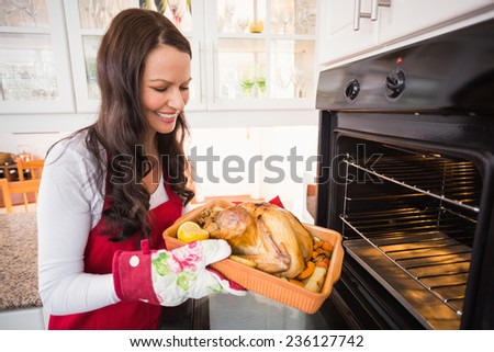 Smiling woman taking out her roast turkey at home in the kitchen - stock photo