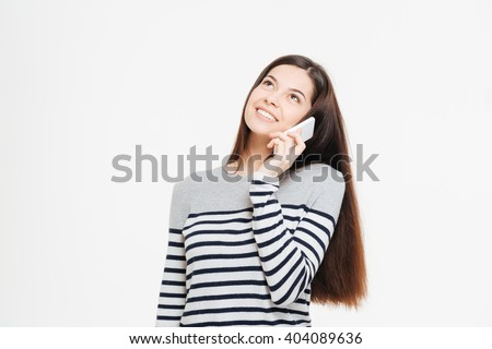 Smiling woman talking on the phone and looking up isolated on a white background - stock photo