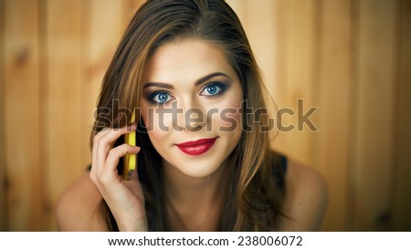 Smiling woman talking phone. Beautiful girl face portrait on wooden background. - stock photo