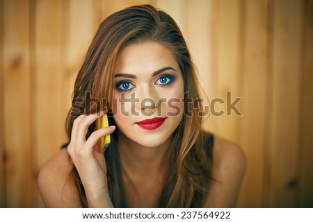 Smiling woman talking phone. Beautiful girl face portrait with evening make up on wooden background. - stock photo