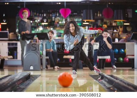 smiling woman throwed the ball at the bowling lane with her supporting friends - stock photo