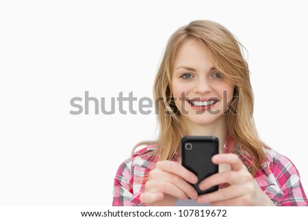 Smiling woman using a mobile phone while looking at camera against a white background - stock photo