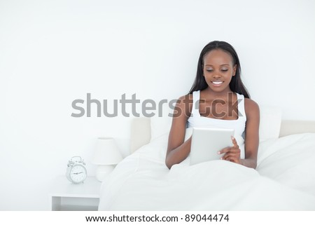 Smiling woman using a tablet computer in her bedroom - stock photo