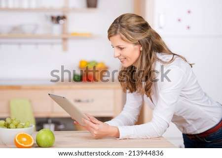smiling woman using digital pad in the kitchen