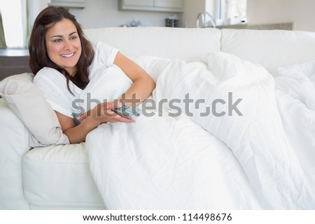 Smiling woman watching television while lying on sofa
