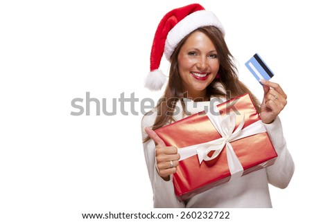 Smiling woman wearing a red Santa hat purchasing Christmas gifts on a bank card holding up a colorful red giftwrapped box with a happy smile and a thumbs up gesture of success, isolated on white - stock photo