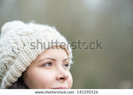 Smiling woman wearing a white knitted woolly cap in winter staring off into the distance lost in thought, with copyspace - stock photo