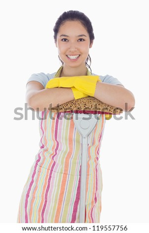 Smiling woman wearing gloves and apron leaning on mop - stock photo
