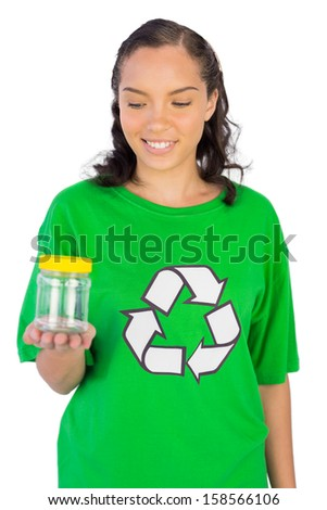 Smiling woman wearing green recycling tshirt holding jar against white background - stock photo