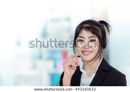 Smiling woman wearing microphone headset as an operator, telemarketer, call center ,hot line and customer service staff .Positive emotion