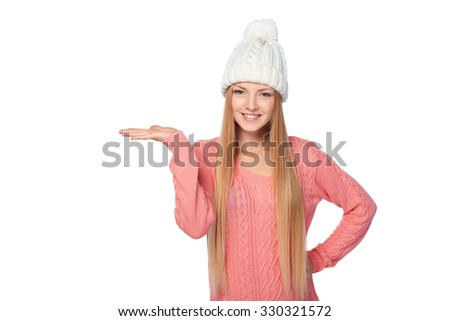 Smiling woman wearing warm knitted winter hat and sweater showing open hand palm with copy space for product or text, over white background
