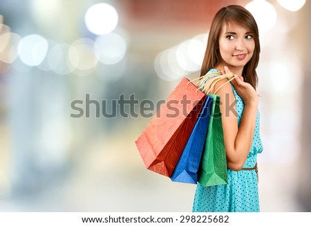 Smiling woman with a gift bag on a light background