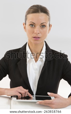 Smiling woman with a tablet computer sitting at a table looking at the camera with copy space - stock photo