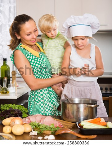 Smiling woman with baby in arms and little daughter cooking together at home kitchen. Focus on girl  - stock photo