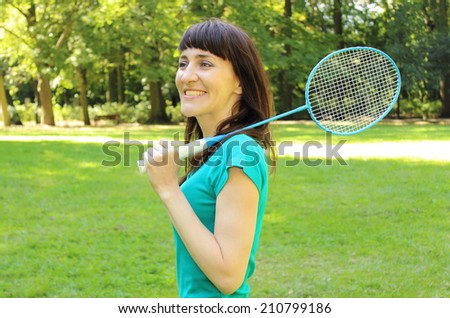 Smiling woman with badminton racket in the sunny park - stock photo