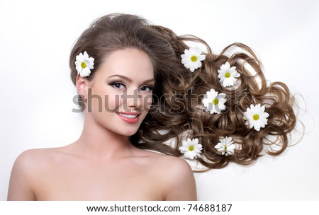 Smiling woman with beautiful long hair with flowers in it - white background - stock photo