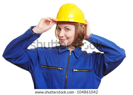 Smiling woman with blue overall putting on safety helmet - stock photo