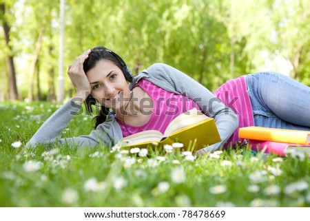 smiling woman with book in nature listening music through headset