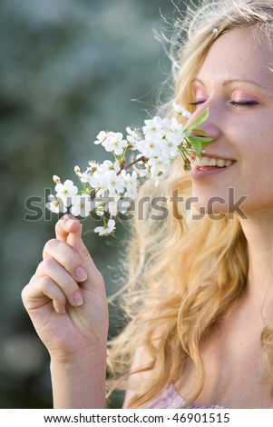 Smiling woman with branch of blooming tree at spring park - stock photo