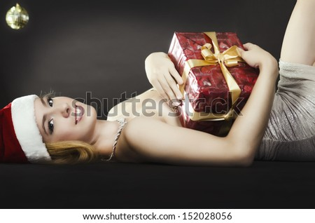 Smiling woman with Christmas gift lying on floor
