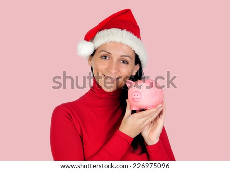 Smiling woman with christmas hat and a pink piggy-bank  - stock photo
