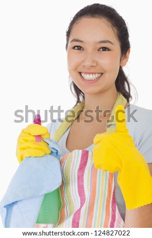 Smiling woman with cleaning products giving thumbs up in rubber gloves - stock photo