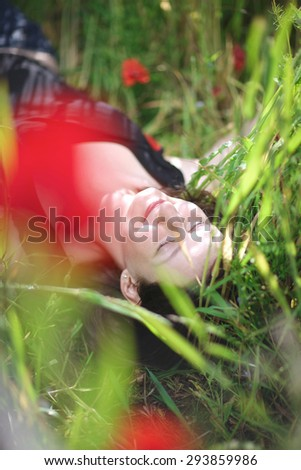 Smiling woman with closed eyes laying in the blooming meadow - stock photo