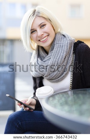 Smiling woman with coffee and using phone outdoor - stock photo