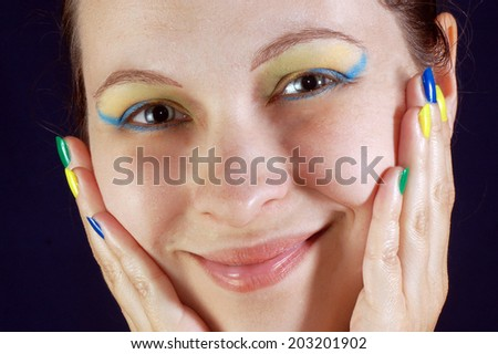Smiling woman with colorful nails and make up with colors of Brazil.