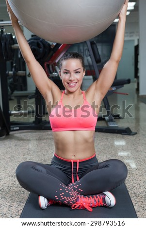 Smiling woman with fitness ball in the gym - stock photo