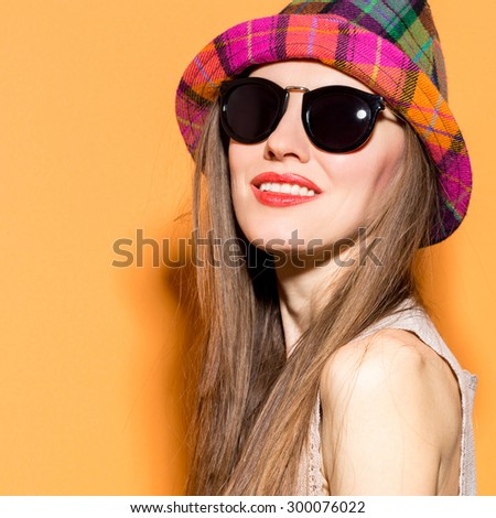 Smiling woman with hat and sunglasses over bright background. studio shot, copy space - stock photo