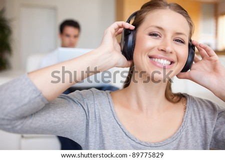 Smiling woman with headphones on with man sitting behind her on the sofa