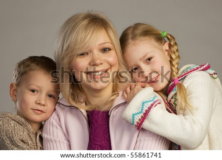 Smiling woman with her children looking into camera, gray background