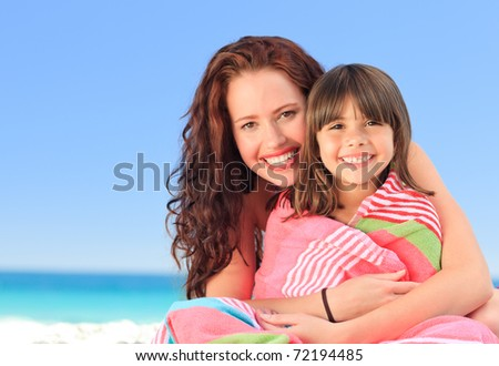 Smiling woman with her daughter in a towel - stock photo