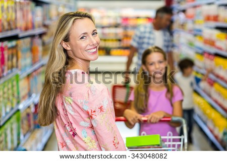 Smiling woman with her family at the supermarket - stock photo